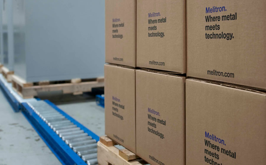 A stack of Melitron-branded cardboard boxes on a wooden pallet are ready to be shipped out of the factory.