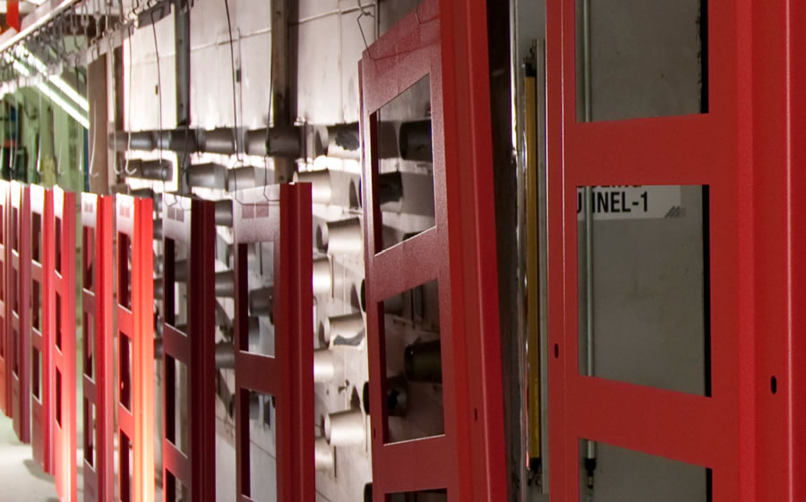 A line of metal enclosure panels on hooks hang to dry after treatment with a red powder-coated finish.
