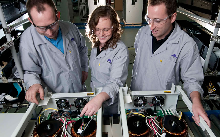 Melitron employees with safety glasses inspect the electro-mechanical assembly within a metal enclosure.