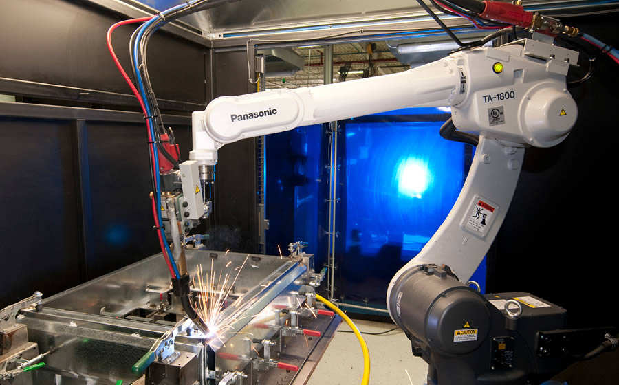 A robotic welding arm makes sparks fly in a welding cell as part of the fabrication of a metal enclosure.